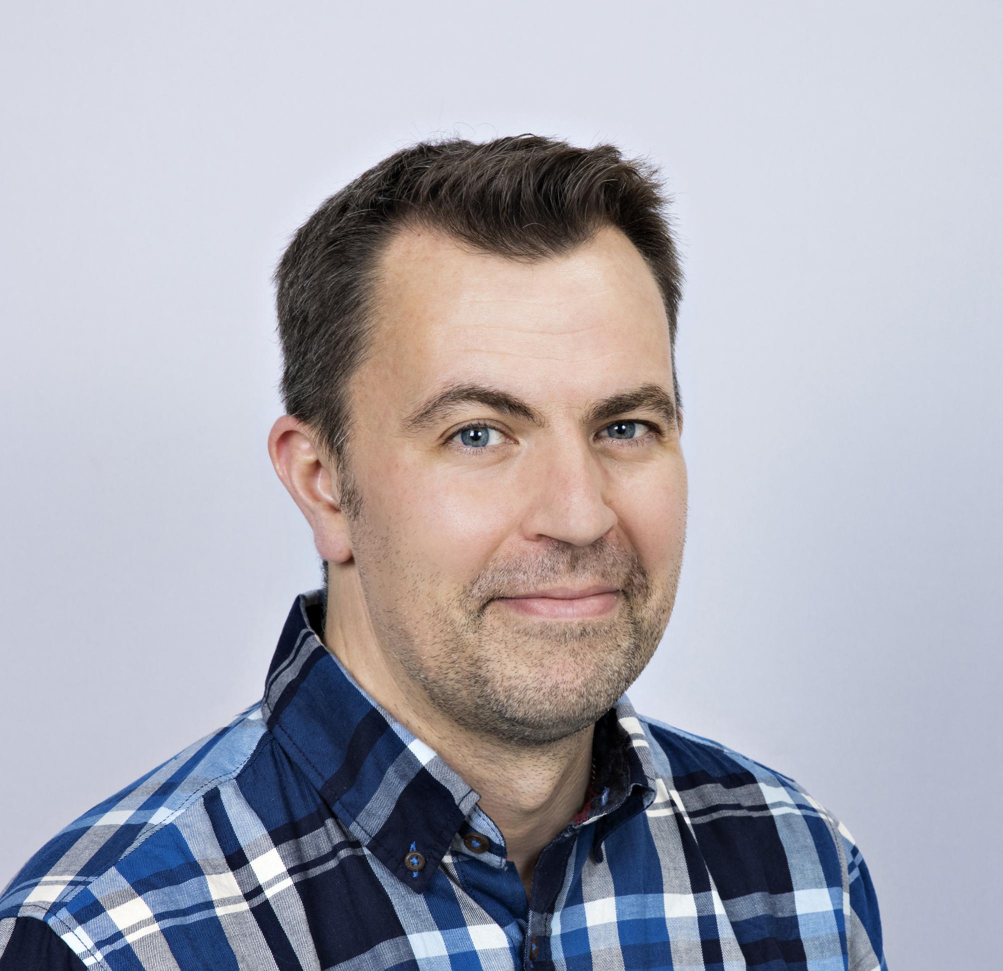Porträtt på Anders Olofsson som ler i en blå- svart- och vitrutig skjorta