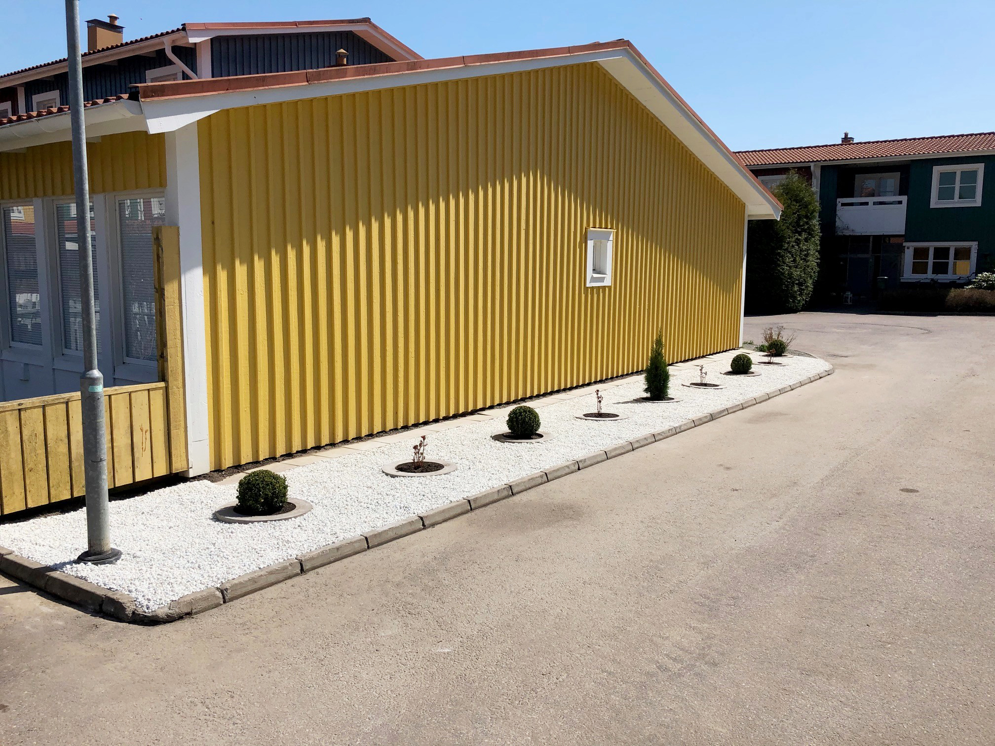Rabatt med vit sten och buskar mot en gul fasad