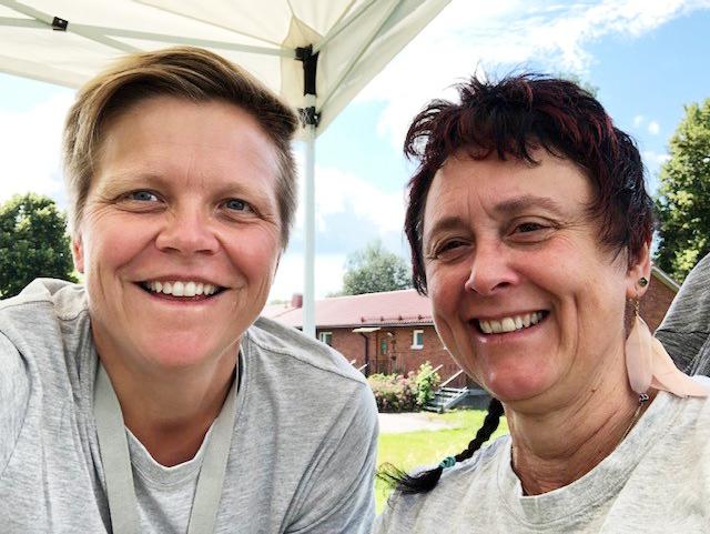 Två leende kvinnor från Salabostäder mot en blå och vitmolning himmel