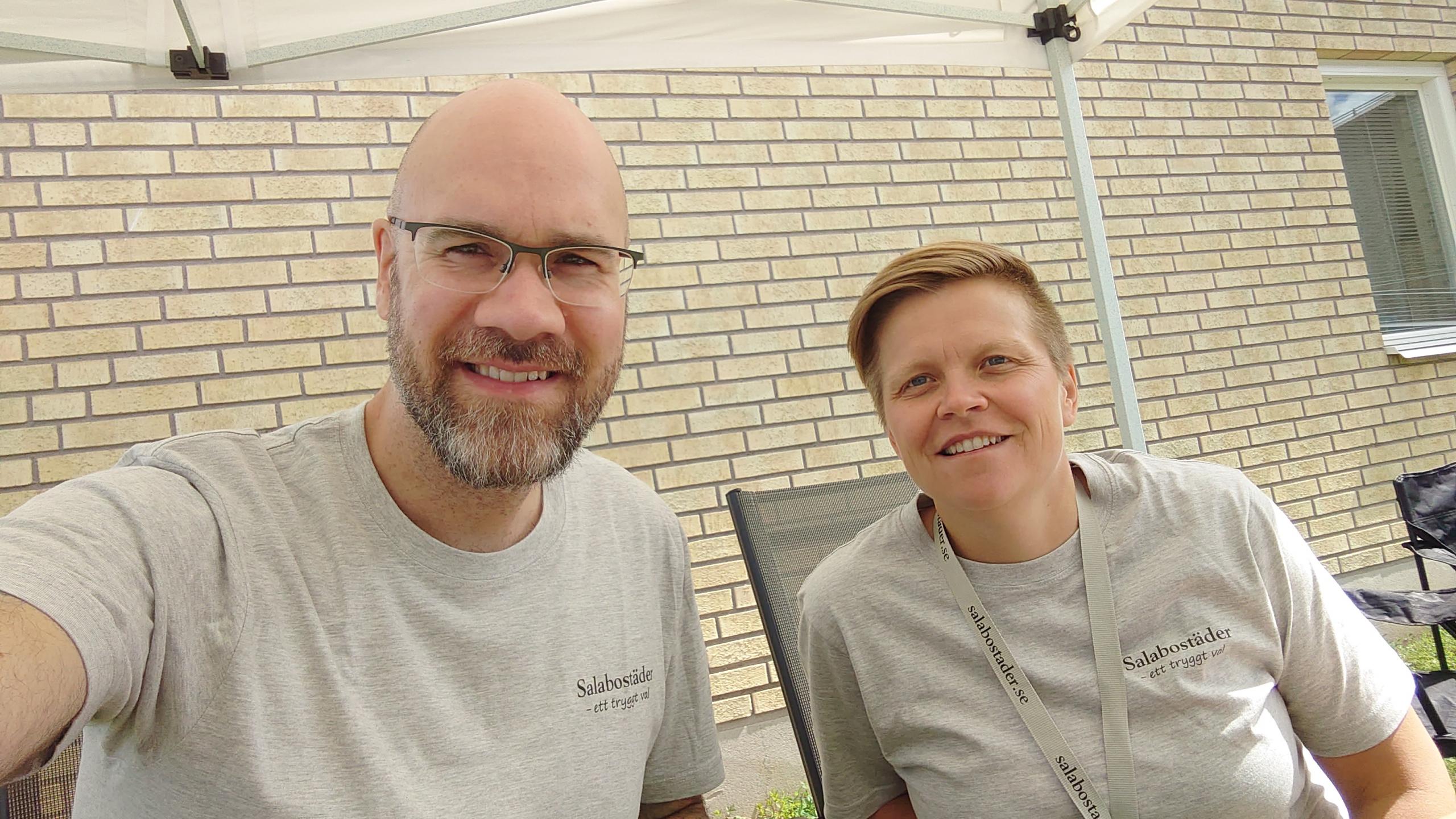 Patrik och Linda ler mot kameran mot en gul tegelvägg