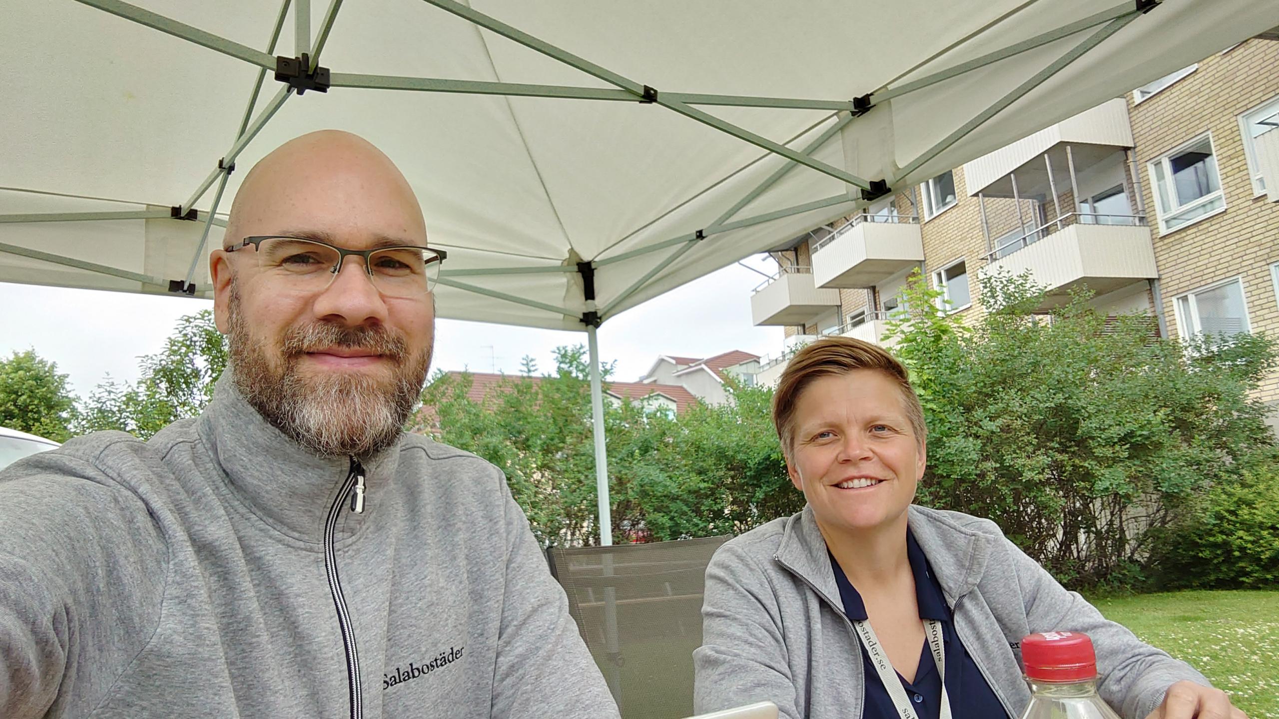 En leende kommunikatör och en leende social samordnare från Salabostäder sitter i ett tält på en innergård