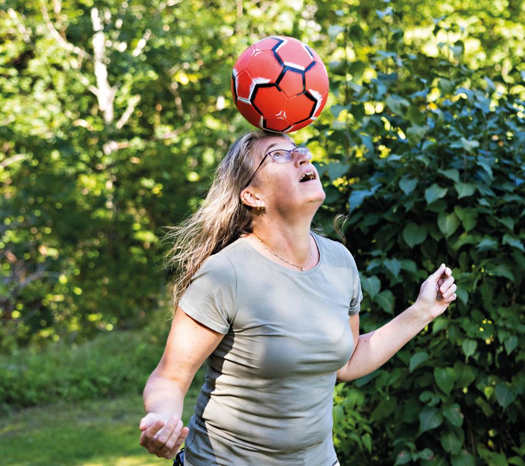 Kvinna i lummig trädgård jonglerar med röd fotboll i pannan.
